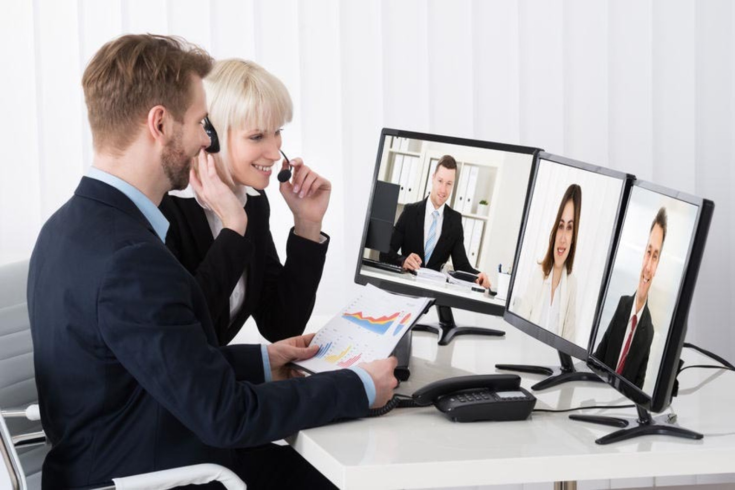 54885331 - two businesspeople video conferencing on desk with multiple computer